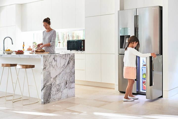 A mother and daughter in the kitchen with Samsung fridge
